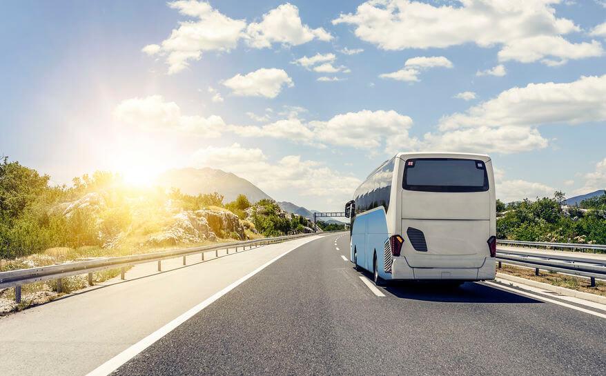 imagen destacada del post sobre recomendaciones para viajar en autobus tras el confinamiento donde aparece un autobús yendo al horizonte